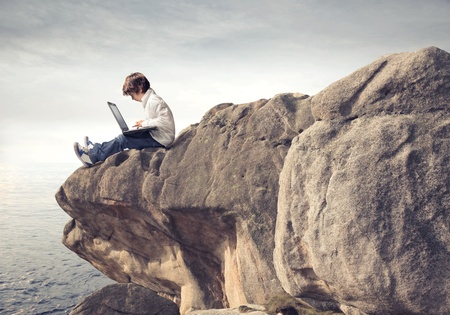 Child sitting on a rock over the sea and using a laptop photo