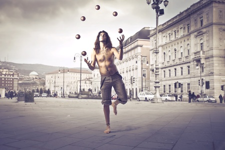 performer: Young man juggling on a city street Stock Photo