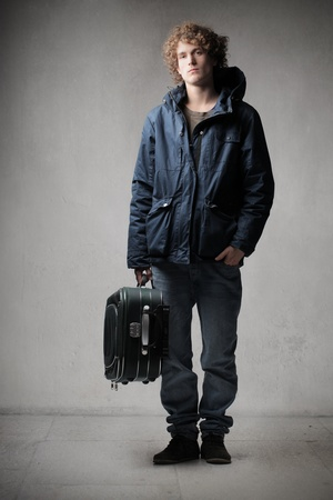 Young man carrying a trolley case photo