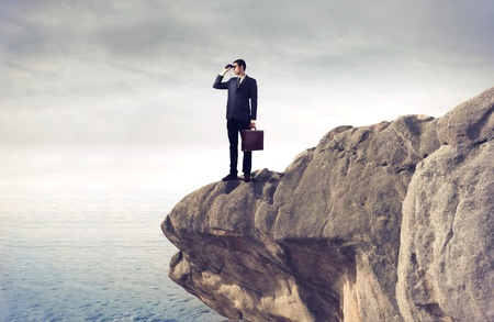 opportunity: Businessman using binoculars on a rock over the sea Stock Photo