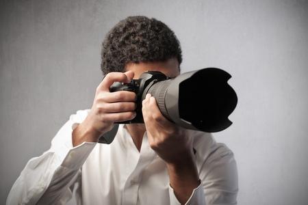 reflex: Fotografia giovane che punta una fotocamera reflex per scattare foto