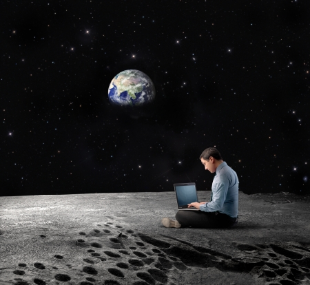 Businessman sitting on the Moon and using a laptop with Earth Planet in the background photo