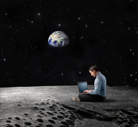 astronomie: Geschäftsmann sitzt auf dem Mond und mit einem Laptop mit Earth Planet im Hintergrund
