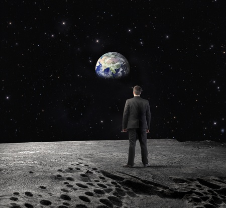 Businessman on the Moon looking at the Earth photo