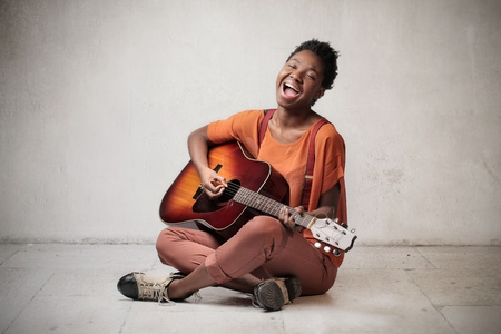 Happy african woman playing the guitar and singing out loud photo