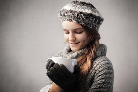Smiling teenage girl in warm clothes holding a bowl of hot drink photo