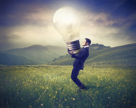 mind powers: Businessman lighting up a green meadow with a giant light bulb Stock Photo