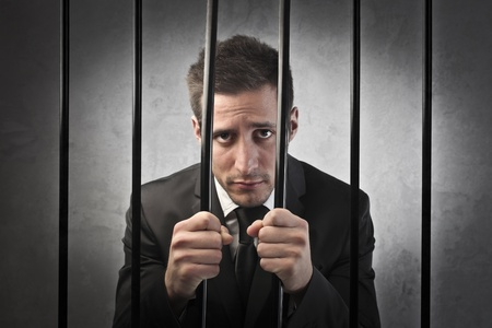 prisoner man: Sad businessman in prison