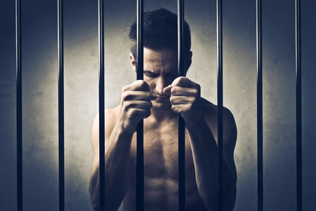 prison system: Sad man in prison Stock Photo