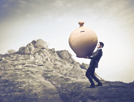 hard way: Businessman carrying a giant money box on a mountain Stock Photo