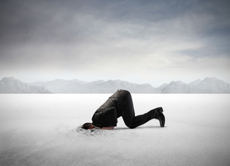 head in the sand: Businessman hiding his head in the sand Stock Photo