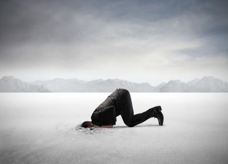 hombre asustado: Empresario ocultando su cabeza en la arena Foto de archivo
