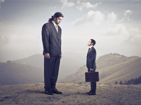 Giant zakenman met inachtneming van een kleinere Stockfoto