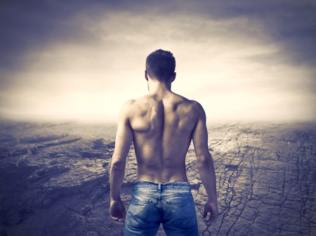 back light: Rear view of a bare-chested muscular man with dried landscape in the background Stock Photo