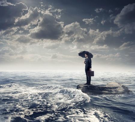 ahogarse: Hombre de negocios bajo un paraguas sobre una roca en medio de un mar ligero bajo el cielo tormentoso Foto de archivo