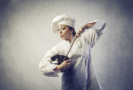 Funny female cook mixing dough in a pot photo