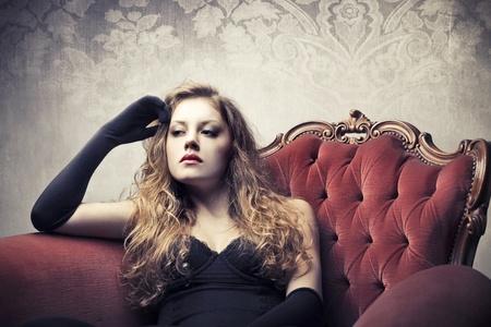 Beautiful elegant woman sitting on a velvet armchair photo