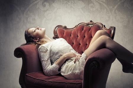 Bella donna sdraiata su una poltrona con posa sensuale