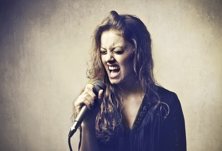 Beautiful woman singing into a microphone photo
