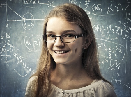 Smiling teenage student with blackboard in the background photo