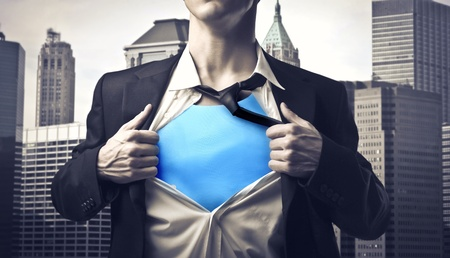 Closeup of a businessman showing the superhero suit under his shirt with cityscape in the background Stock Photo - 12394089