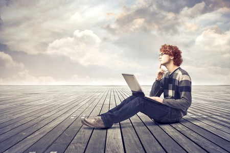 minds: Young man with thoughtful expression sitting on a parquet floor and using a laptop Stock Photo