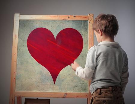 Child drawing a heart on a blackboard photo