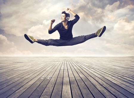 danza moderna: Sonriente joven de baile a la música a través de un suelo de parquet Foto de archivo