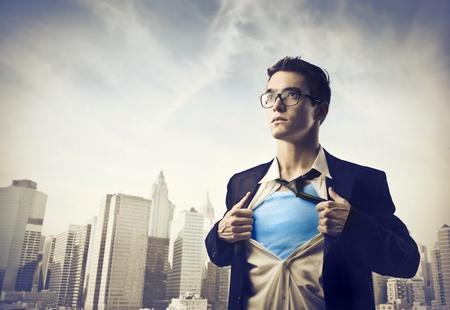 Joven hombre de negocios que muestra el traje de superhéroe bajo su camisa con paisaje urbano en el fondo