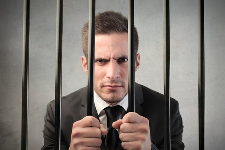 culpable: Businessman behind bars Stock Photo