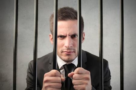culpable: Businessman behind bars Stock Photo
