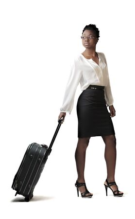 mujer con maleta: Empresaria africana cargando una maleta con ruedas
