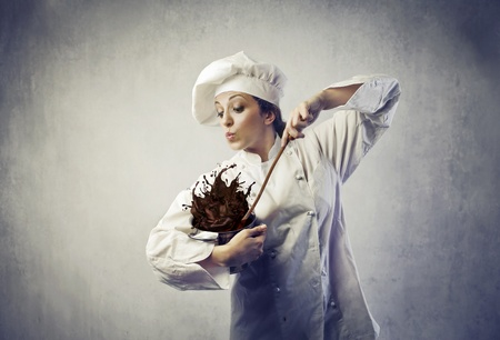female portrait: Funny female cook mixing some chocolate spilling from the pot Stock Photo