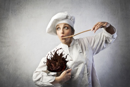 Funny female cook tasting some chocolate cream spilling from a pot