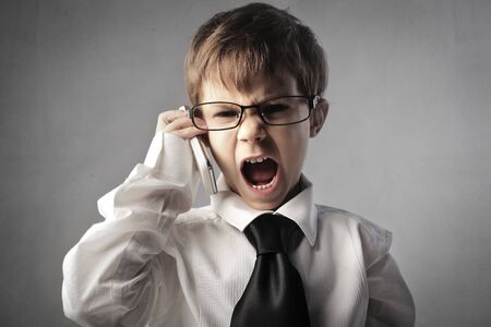 Angry child disguised as a businessman screaming on the mobile phone Stock Photo - 12394126