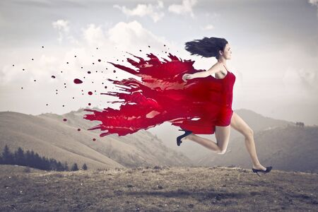 Beautiful woman running on a hill with her dress melting in red paint photo