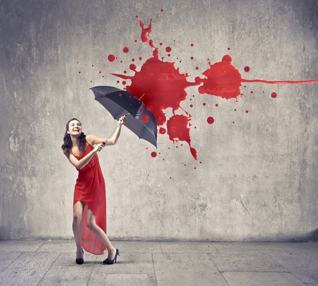 Laughing beautiful woman using an umbrella as a shelter against paint drops falling down photo