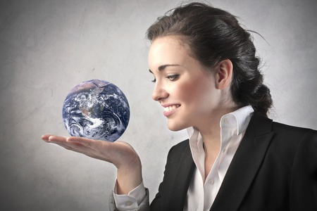 Smiling businesswoman holding the Earth in her hand photo