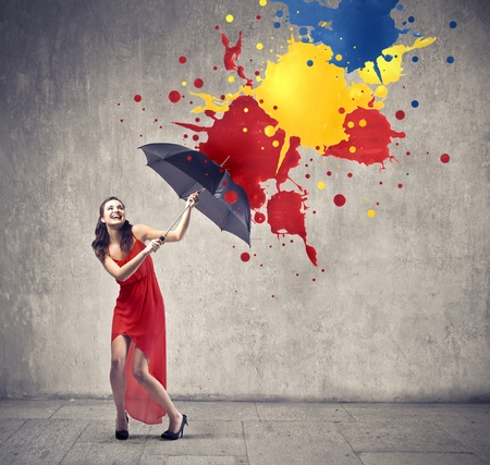 woman with umbrella: Laughing beautiful woman using an umbrella as a shelter against paint drops falling down