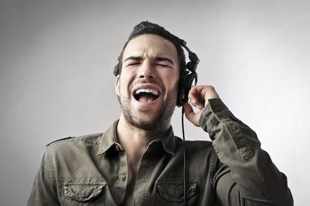 singing: Young man singing while listening to music