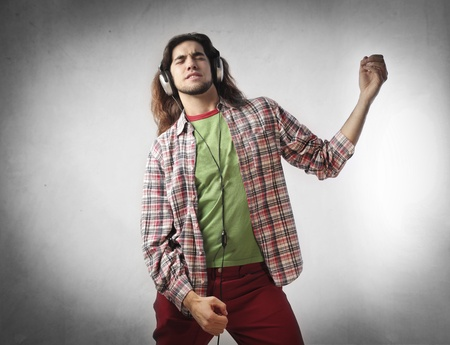 air guitar: Young man listening to music and playing air guitar