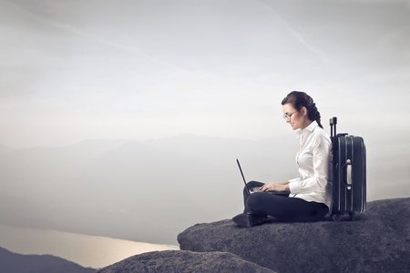 Businesswoman sitting on a rock over a lake against a suitcase and using a laptop Stock Photo