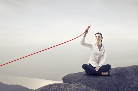Smiling businesswoman sitting on a rock over a lake and charting a positive trend graph Stock Photo - 12647450