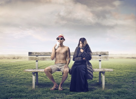 different concept: Smiling man in bathing suit sitting on a bench beside a woman wrapped in warm clothes Stock Photo