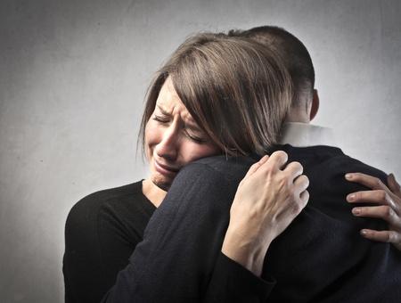 Sad woman crying on her husband s shoulder photo