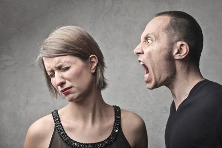 enojo: El hombre gritando en contra de su esposa triste