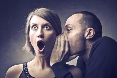 El hombre dice un secreto a una mujer asombrada