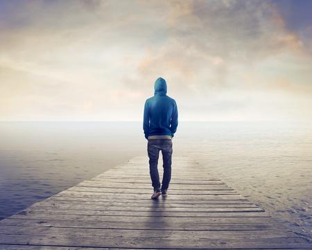 Jeune homme marchant sur un quai sur la mer Banque d'images