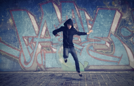 graffiti art: Young man jumping with graffiti in the background Stock Photo