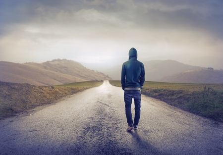 loin: Jeune homme marchant sur une route de campagne